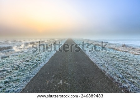Desolate road in a winter rural landscape in Holland - stock photo