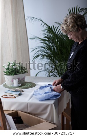 Despair senior woman packing dead husband's clothes - stock photo