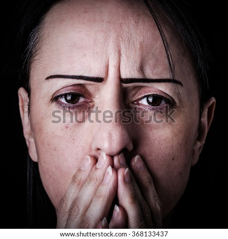 Despair, shock. Woman with her hands over her mouth, looking worried towards viewer.  - stock photo