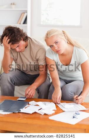 Despaired worn out couple calculating their expenses in the living room - stock photo