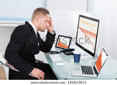 Despairing businessman faced with financial losses sitting at his desk consulting three graphs on different monitors all dropping into the red - stock photo