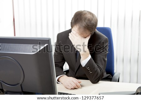 Despairing businessman sitting at his desk in his office resting his forehead in his hands as he considers the hopelessness of the situation - stock photo