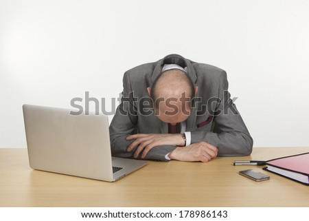 Despairing businessman with his head down resting on his arms on his desk as he contemplates the hopelessness of his position - stock photo