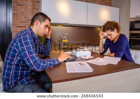 Desperate and unemployed young couple reviewing their credit card debts. Financial family problems concept. - stock photo