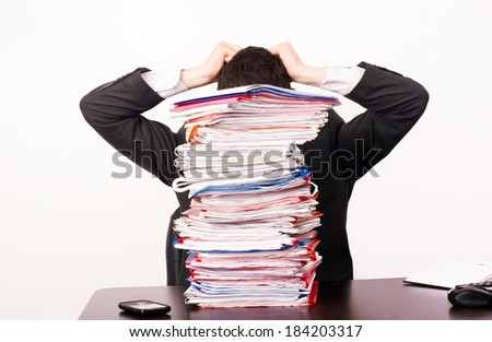 Desperate business man with a lot of work. Unhappy worker with a big pile of files to work on. - stock photo