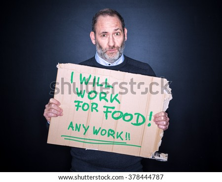 Desperate Businessman holding a cardboard sign Looking for a job in his Hands, will work for food - stock photo