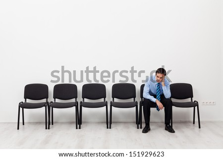 Desperate businessman or employee sitting alone propping his head - stock photo