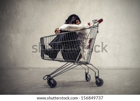desperate businessman sitting in the shopping cart - stock photo
