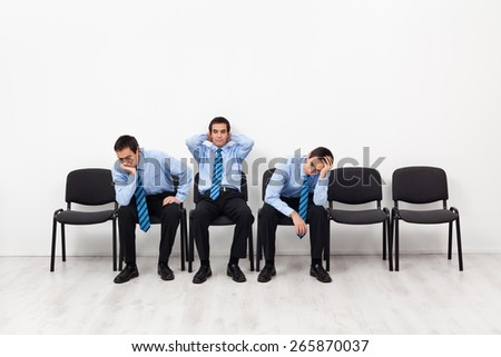 Desperate businessmen sitting on chairs having doubts about the future - stock photo