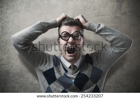 Desperate funny guy with head in hands screaming - stock photo