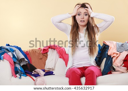 Desperate helpless woman sitting on sofa couch in messy living room with hands on head. Young girl surrounded by many stack of clothes. Disorder and mess at home. - stock photo