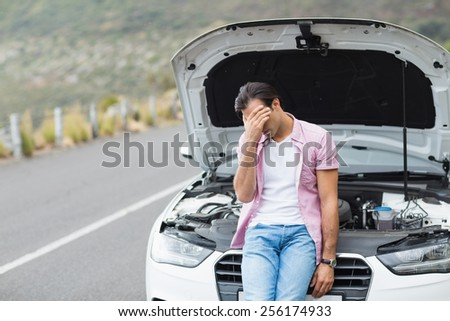 Desperate man after a car breakdown at the side of the road - stock photo