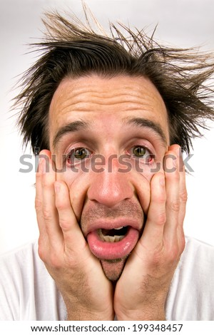 Desperate man holding his face in hands appears in a miserable state of unhappiness. - stock photo