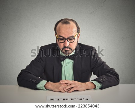 Desperate middle aged businessman sitting at desk looking down at stress sign isolated office grey wall background. Negative human emotion, feelings - stock photo