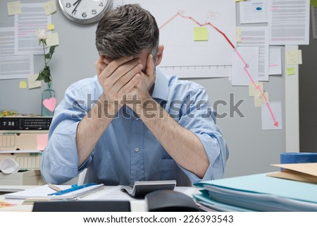 Desperate office worker with head in hands and negative financial chart on background. - stock photo