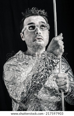 Desperate spaceman holding rope. - stock photo