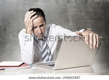 desperate tired senior businessman in crisis working on computer laptop at office desk in stress under pressure facing work problems on grunge studio edition - stock photo