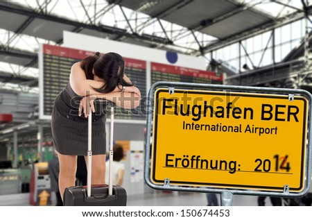 desperate woman and shield and the german words Berlin Brandenburg Airport / BBI airport - stock photo