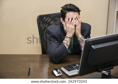 Desperate, worried young businessman sitting at his desk in front of his computer with his face in his hands and eyes closed - stock photo