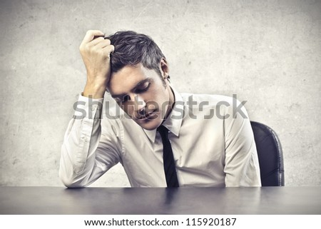 Desperate young businessman leaning on a desk - stock photo