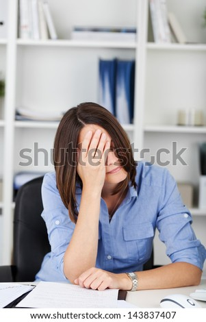 Despondent businesswoman sitting at her desk resting her head in her hand covering her eyes - stock photo
