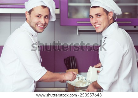 Dessert cooking concept. Portrait of smiling male chefs cooking food and standing in the modern kitchen of restaurant. Indoor shot - stock photo
