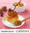 Dessert from a pear with honey in a puff test on a background a nuts and checked table-cloth - stock photo