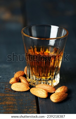 Dessert liqueur Amaretto with almond nuts, on dark wooden table - stock photo