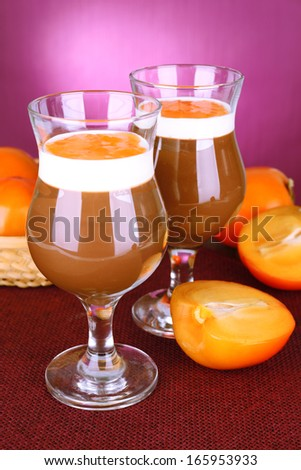 Dessert of chocolate and persimmon on table on purple background - stock photo