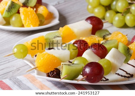 Dessert of fresh fruit on skewers on a white plate close-up. horizontal  - stock photo