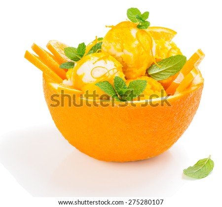 Dessert of orange ice cream decorated with leaves of mint in a rind of orange fruit isolated on white background - stock photo
