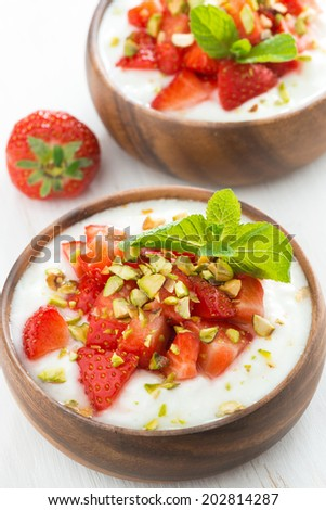 dessert of yogurt with fresh strawberries, pistachios and mint, top view, close-up - stock photo