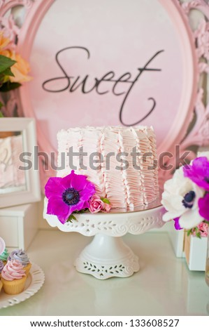 Dessert table for a party. Ombre cake and flowers - stock photo