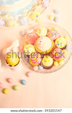 Dessert table set with cake and cupcakes for Easter brunch. - stock photo