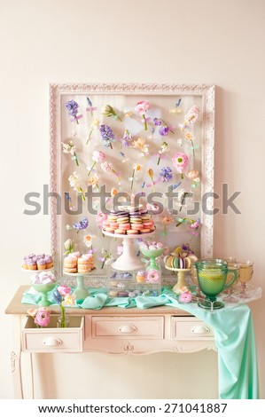 Dessert table with a large macaroons composition - pyramid in pink, decorated with flowers. - stock photo