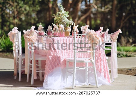 Dessert table with cakes decorated for a kids outdoor party - stock photo