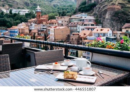 Desserts and tea served in a terrace of restaurant. Tbilisi old city on background - stock photo