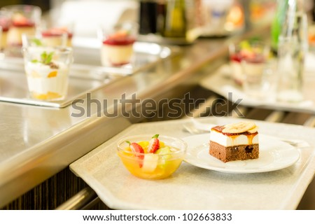 Desserts on serving tray cafeteria self service fruit salad cake - stock photo