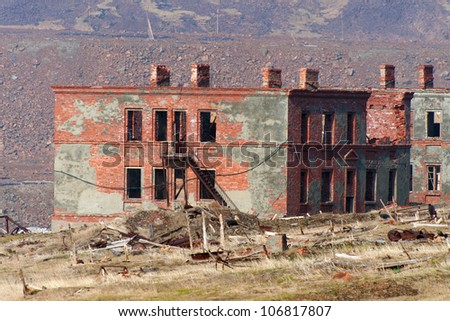 Destroyed a two-story brick building on the background of the mountains. - stock photo