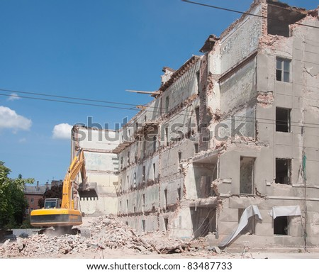 Destroyed building and bulldozer, demolition, earthquake, bomb, catastrophe, disaster. - stock photo