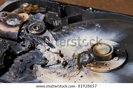 destroyed hard drive in close up view. The read write head is melted - stock photo
