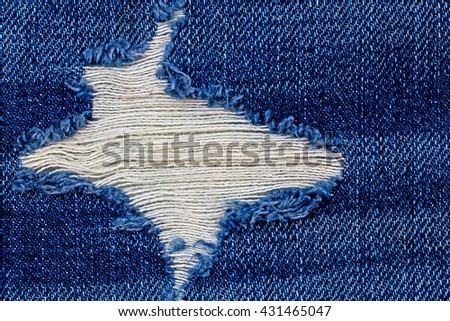 Destroyed torn blue denim jeans patch close up - stock photo