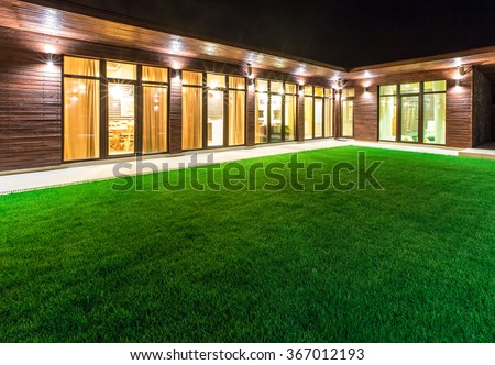 Detached house at night view from outside the rear courtyard.  - stock photo
