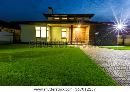 Detached luxury house at night view from outside front entrance.  - stock photo