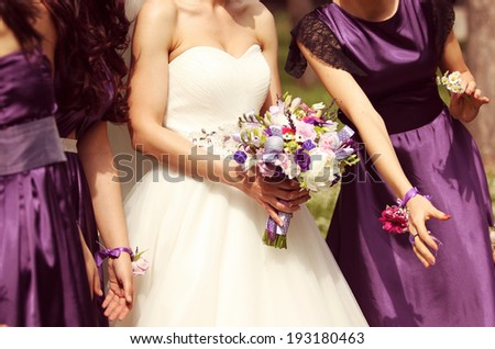 Detail and bride and bridesmaid with flowers - stock photo