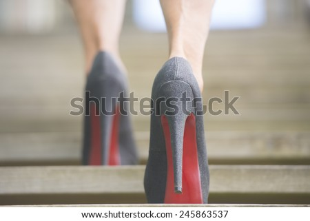 Detail close up of upward view of woman in high heel stiletto shoes walking up wooden stairs with blurred background. - stock photo