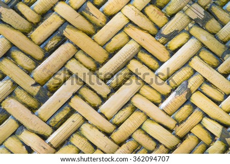 Detail close up view of a uniform golden woven basket using natural branch materials.Pattern of Thai style bamboo handcraft texture background  - stock photo