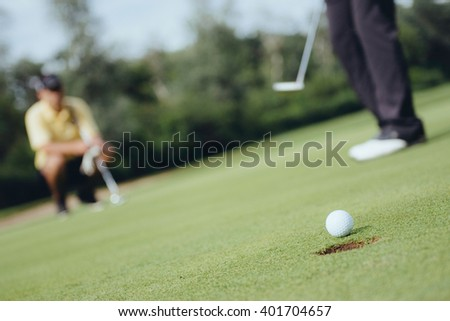Detail from game of golf. Focus on ball, golfers in background, toned image - stock photo