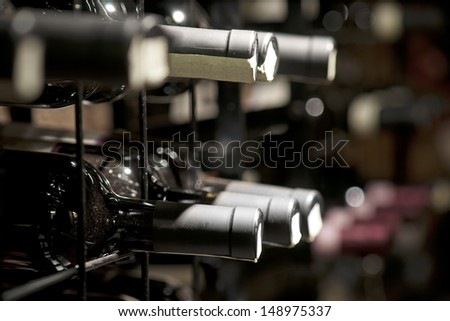 Detail from wine cellar with resting bottles - stock photo