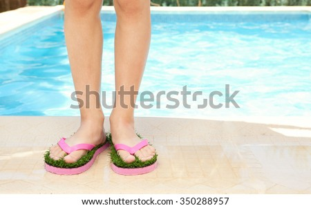 Detail girl child feet wearing a pair of humorous fun pink sandals with grass sole, standing by edge of swimming pool in home garden with wet skin on a summer holiday. Kids active lifestyle outdoors. - stock photo